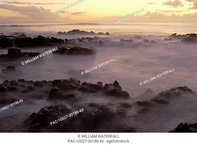 Hawaii, Molokai, Kau Poa beach, Lava rocks in foggy layer over pale sunrise water