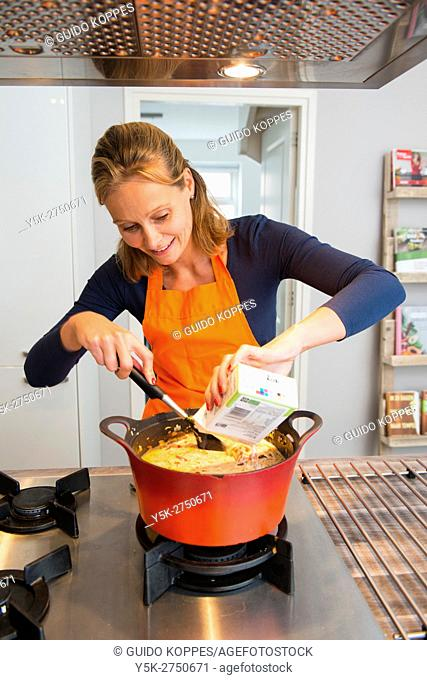 Kaatsheuvel, Netherlands. Mid adult woman adding a sauce to her red colored saucepan, in preparation to a Lasagna dish dinner
