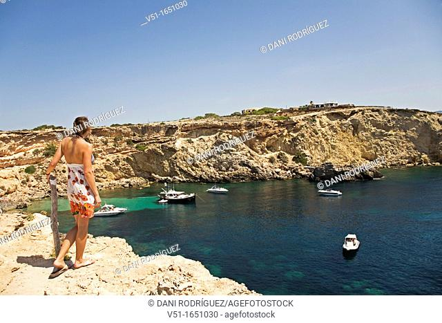 Back view of a woman looking at the beautiful landscape in Ibiza