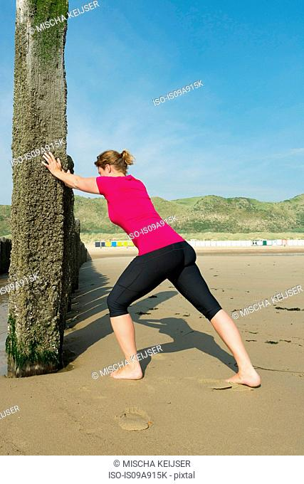 Woman stretching against structure on beach