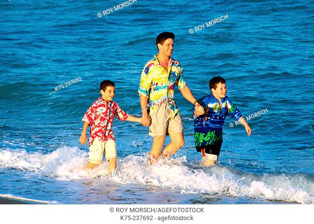 Boys walking through the waves with dad
