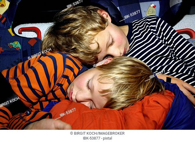 Exhausted children 8 and 10 years old sleeping in the car in the security seats