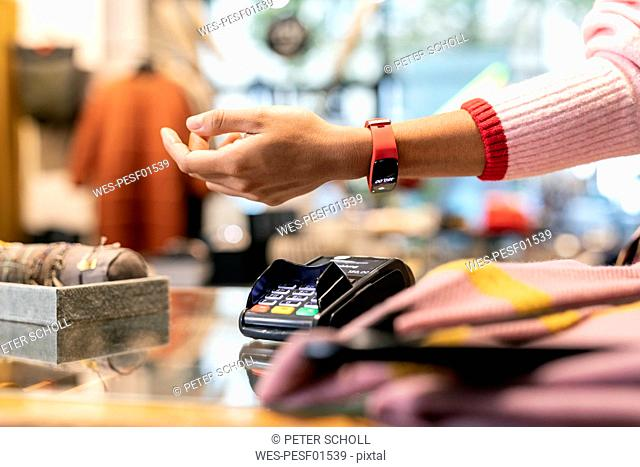 Customer paying contactless with her smartwatch