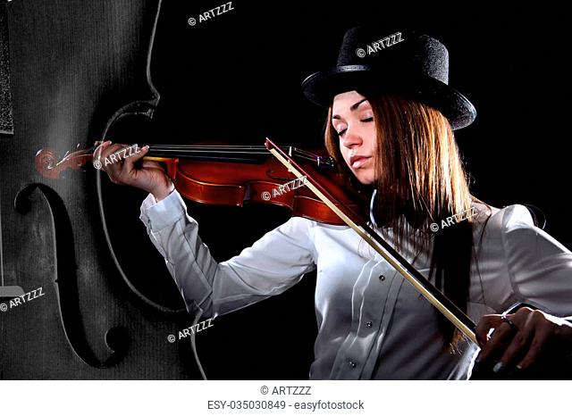 Beautiful young violinist playing a violin over black background