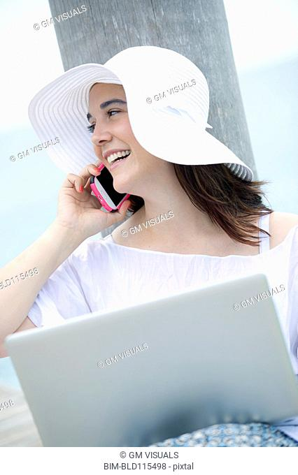 Hispanic woman using cell phone and laptop