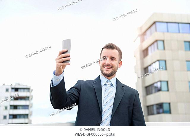 Smiling businessman taking a selfie in front of office building
