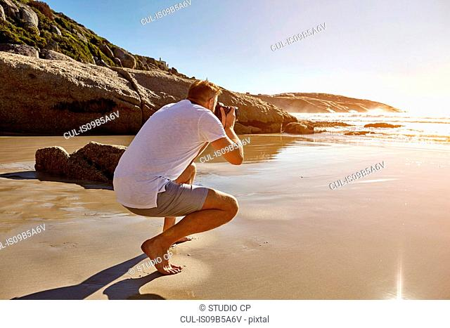 Mature man crouching on beach, photographing view, Cape Town, South Africa