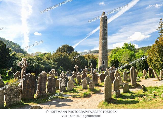 Round tower and gravestones at the historic site of Glendalough, County Wicklow, Ireland, Europe