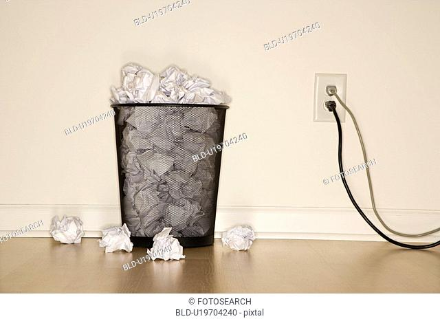 Full wire mesh trash can with crumpled paper next to electrical outlet and plugs