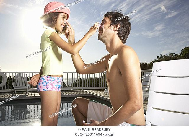 Man and girl applying sun block to noses