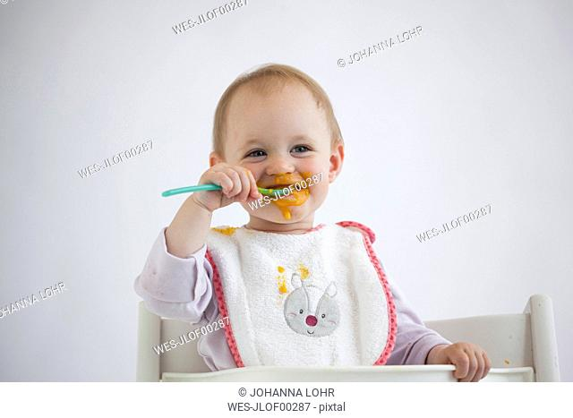 Portrait of smeared baby girl on high chair eating mush