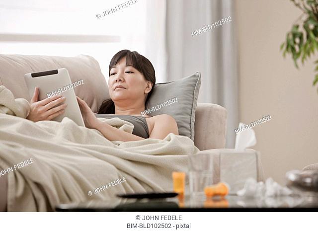 Sick Asian woman using digital tablet on sofa