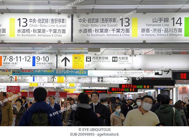 Shinjuku inside JR Shinjuku train station crowd of passengers walking under jumble of train signs bilingual signs