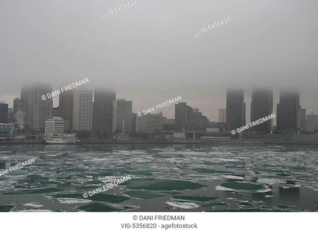 Fog on a cold rainy day shrouds the skyline of downtown Detroit, Michigan, USA. Chunks of ice can be seen floating along the Detroit River