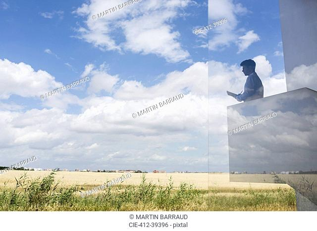 Silhouette businessman writing on modern balcony overlooking sunny blue sky and clouds