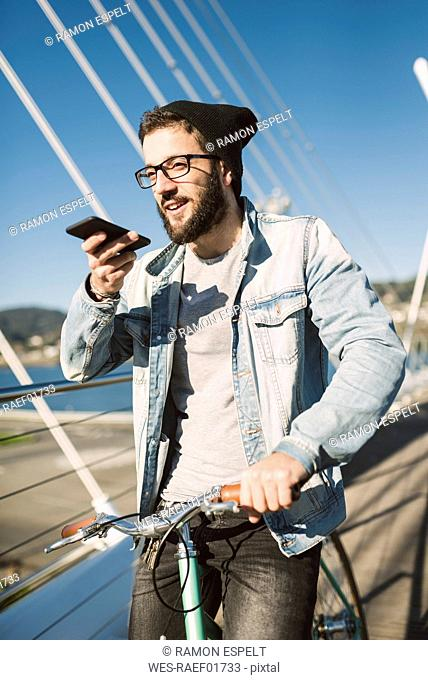 Young man with fixie bike on a bridge using smartphone