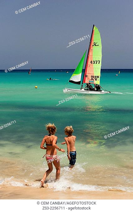Children playing in the sea with the windsurfers and a catamaran in the background, Fuerteventura, Canary Islands, Spain, Europe