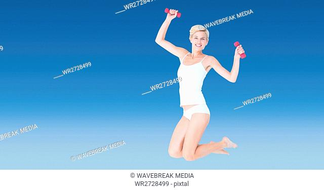 Fit woman with dumbbells jumping against blue background