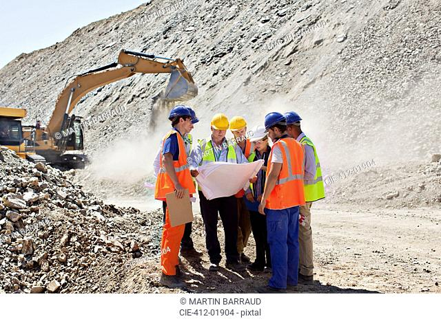 Business people and workers talking in quarry