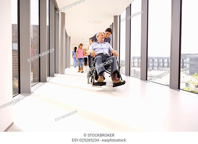 Nurse Pushing Senior Patient In Wheelchair Along Corridor