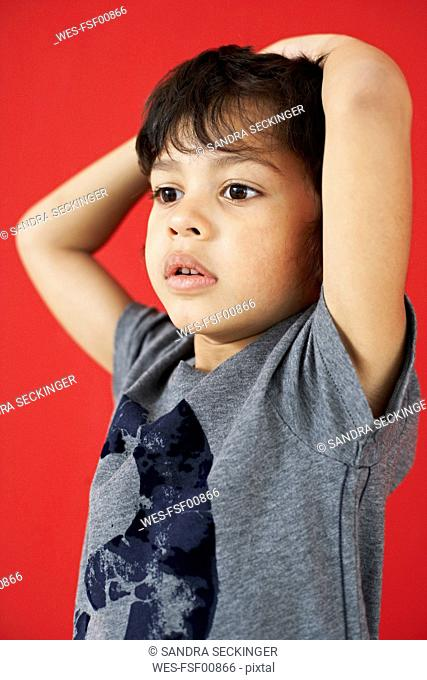 Portrait of little boy with hands on his head in front of red background