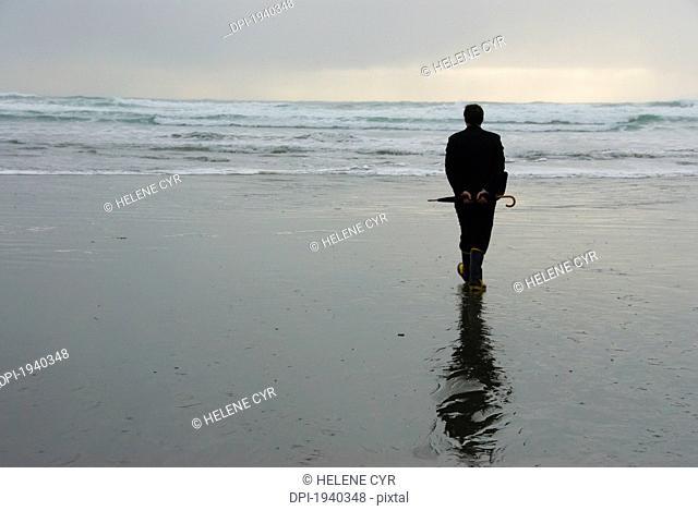 a man on a wet beach holding an umbrella, tofino british columbia canada