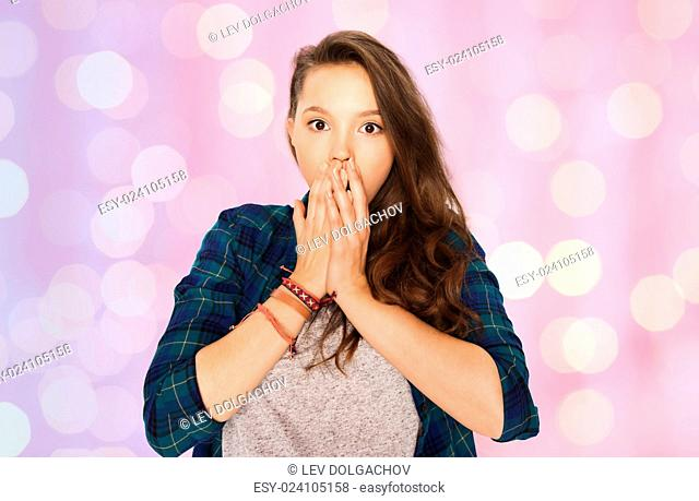 people, emotion, expression and teens concept - scared or surprised teenage girl over pink holidays lights background
