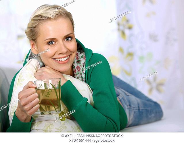 woman lying on sofa drinking a glass of tea