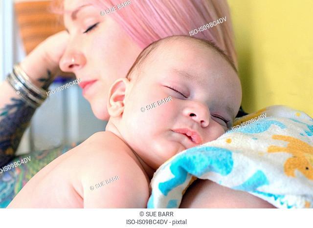 Woman asleep with sleeping baby boy on shoulder