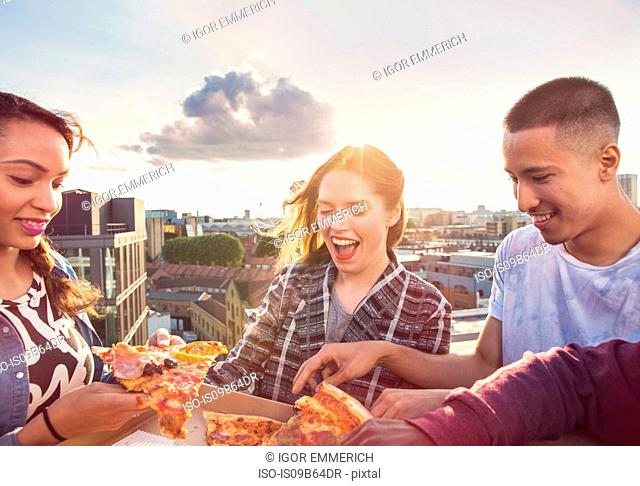 Young adult friends sharing pizza at roof party in London, UK