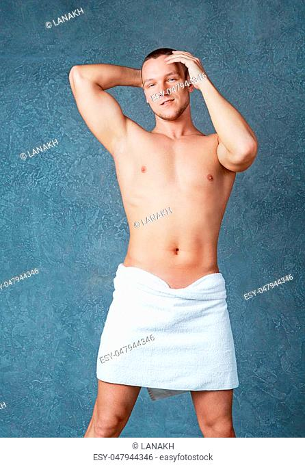 attractive muscular young man with a towel on his hips after shower