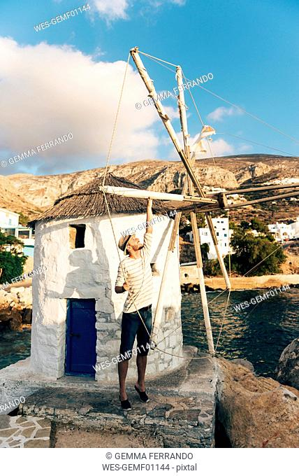 Greece, Amorgos, Aegialis, man holding the the blades of wind mill