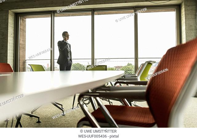 Conference room with businessman on the phone