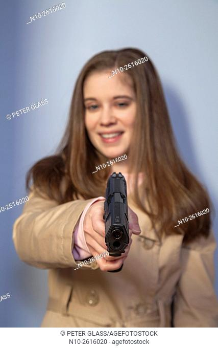 Young woman, wearing a trench coat, holding a gun