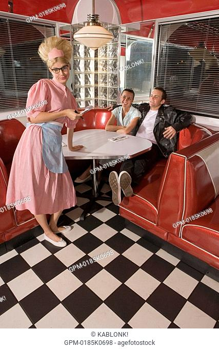 Portrait of young waitress in 1950s style uniform taking order from young couple at old-fashioned diner