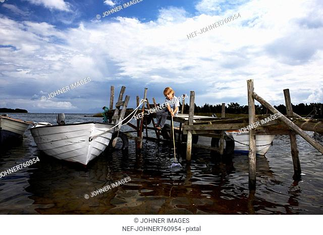 A boy with a bag net on a jetty, Sweden