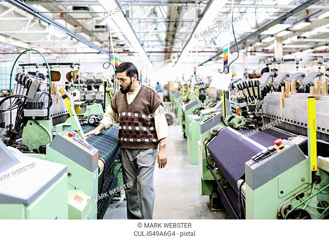 Male factory worker monitoring weaving machine quality in woollen mill
