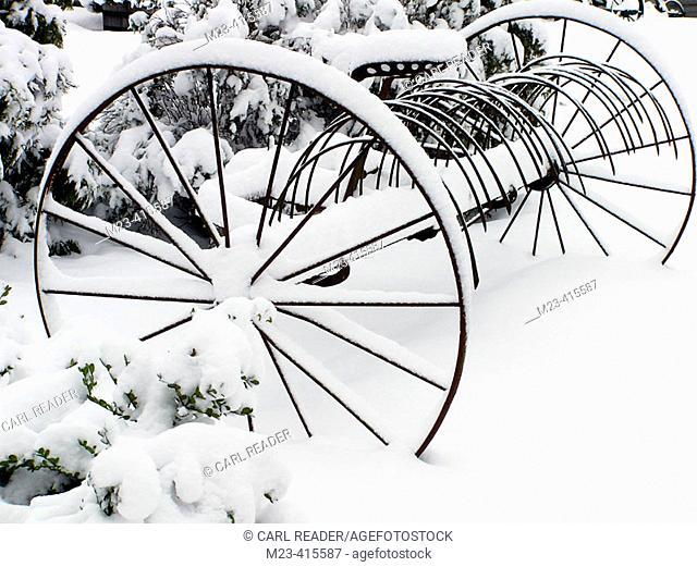 Winter snow covers some antique farm equipment
