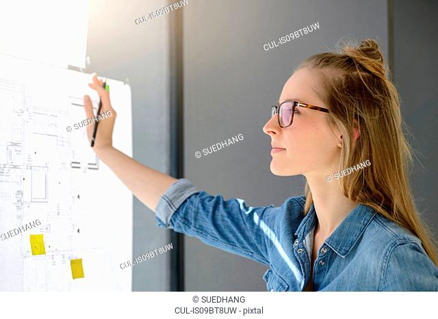 Woman contemplating plans on glass wall