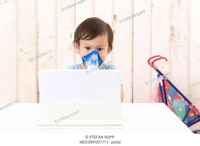 Girl using inhaler looking at digital tablet