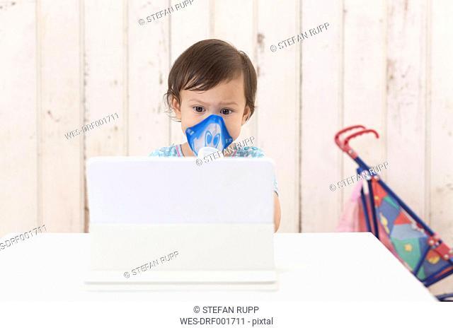 Girl using inhaler looking at digital tablet