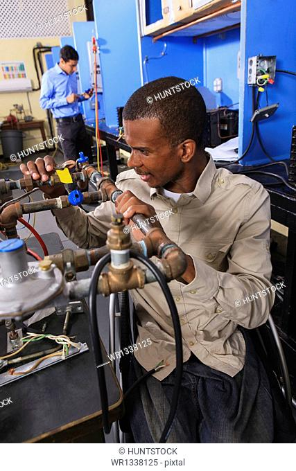 Student in wheelchair examining fuel control valves on furnace in HVAC classroom
