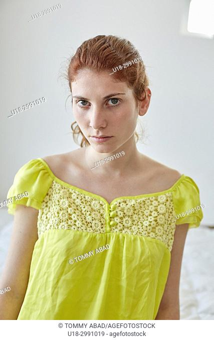 Serious looking young redhead woman wearing yellow dress