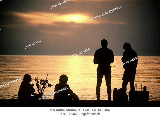 Two couples picnic on the beach watching the sun set and sharing food