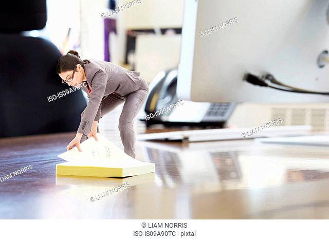Businesswoman using large adhesive label on oversized desk