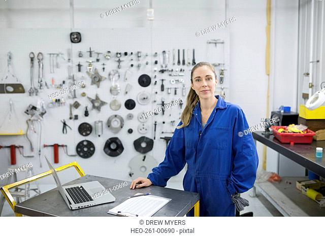 Portrait female helicopter mechanic at laptop in workshop