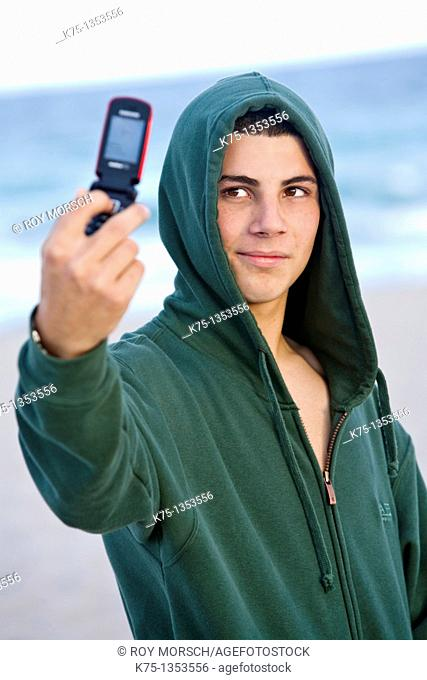 Teen taking photo of himself with camera phone at the beach