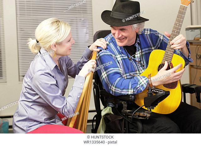 Musician with Multiple Sclerosis in a motorized wheelchair with his guitar playing for a friend