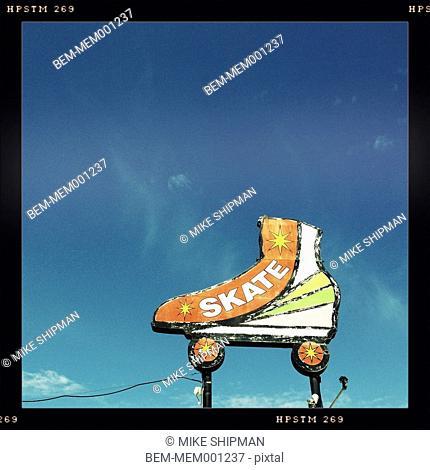 Neon roller skate sign in blue sky