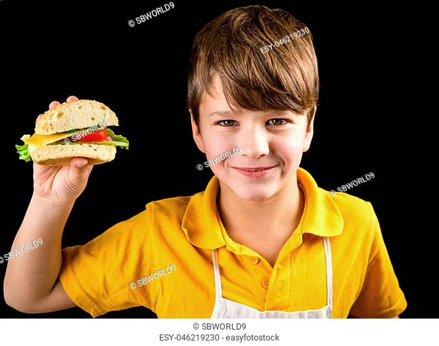 Smiling boy showing sandwich in hand, isolated on black background